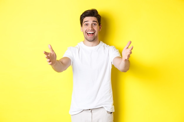 Opgewonden knappe kerel die zijn handen naar voren strekt, reikt naar omhelzing, cadeau ontvangt, staande over gele achtergrond.