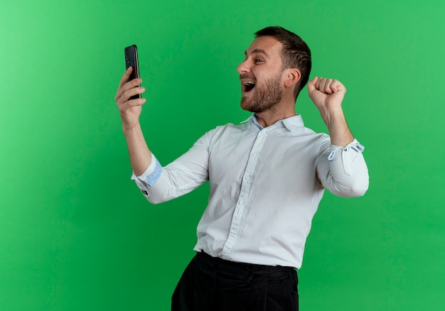 Opgewonden knappe man houdt en kijkt naar telefoon heft vuist geïsoleerd op groene muur