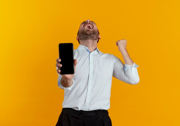 Opgewonden knappe man houdt telefoon heft vuist opzoeken geïsoleerd op oranje muur