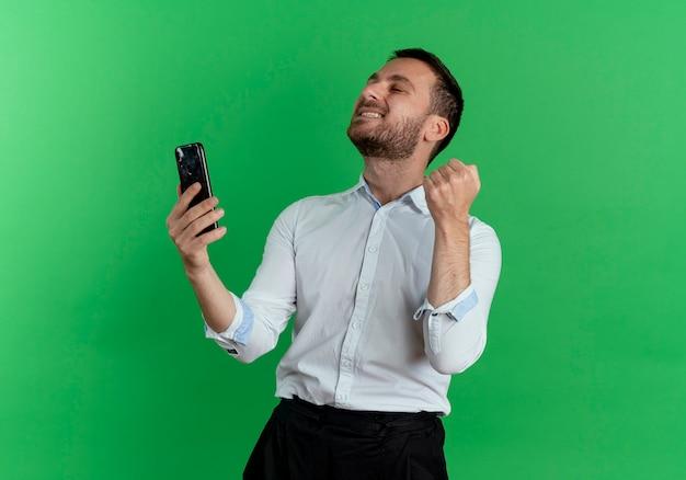 Opgewonden knappe man houdt telefoon vast en houdt vuist opzoeken geïsoleerd op groene muur