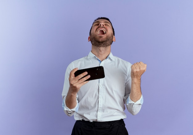 Opgewonden knappe man houdt vuist en houdt telefoon opzoeken geïsoleerd op paarse muur