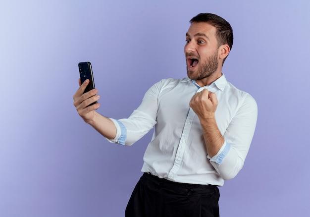 Opgewonden knappe man kijkt naar telefoon en houdt vuist geïsoleerd op paarse muur