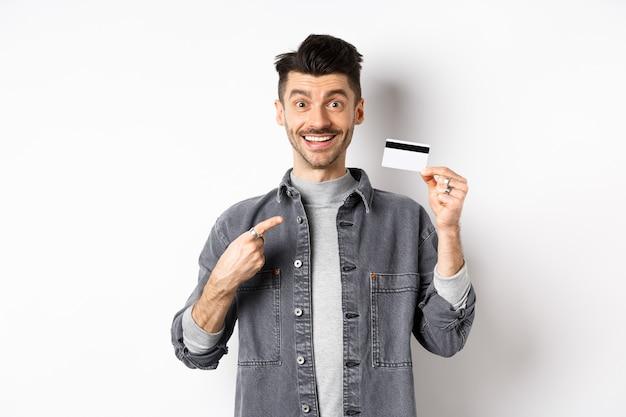Opgewonden knappe man met snor wijzende vinger naar plastic creditcard, glimlachend tevreden, goede deal aanbevelen, staande op een witte achtergrond.
