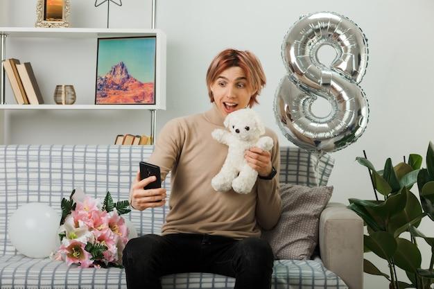 Opgewonden knappe man op een gelukkige vrouwendag met een teddybeer die naar de telefoon in zijn hand kijkt terwijl hij op de bank in de woonkamer zit