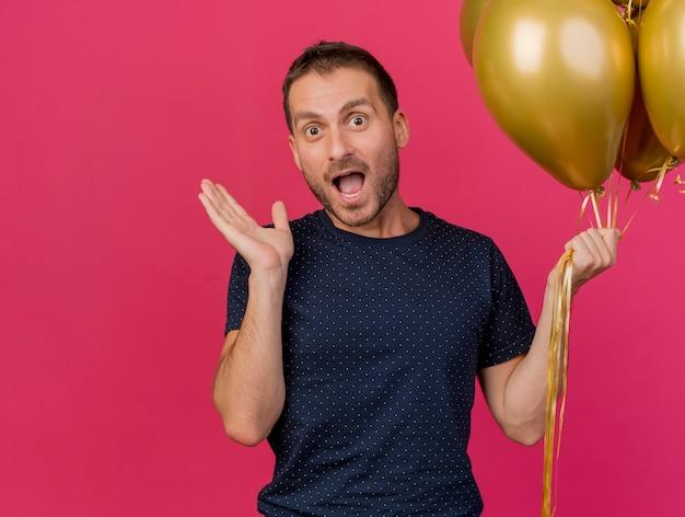 Opgewonden knappe man staat met opgeheven hand en houdt helium ballonnen geïsoleerd op roze muur