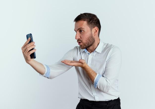 Opgewonden knappe man stuurt kus met hand houden en kijken naar telefoon geïsoleerd op een witte muur