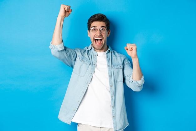 Opgewonden knappe man triomferen, handen opsteken en schreeuwen van vreugde, overwinning vieren, staande tegen een blauwe achtergrond
