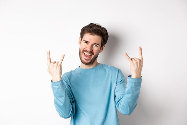 Opgewonden knappe man vieren, plezier hebben en rock op hoorns gebaar tonen, enjoing partij, glimlachend in de camera, staande op een witte achtergrond.