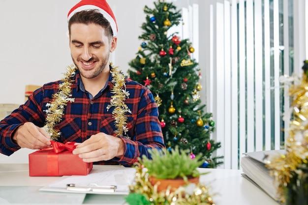 Opgewonden knappe zakenvrouw die kerstcadeau uitpakt terwijl hij aan zijn kantoortafel zit