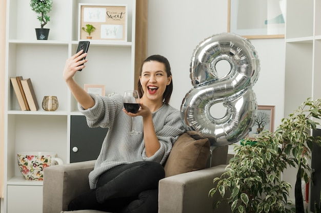 Opgewonden knipperde mooi meisje op een gelukkige vrouwendag met een glas wijn en neem een selfie zittend op een fauteuil in de woonkamer