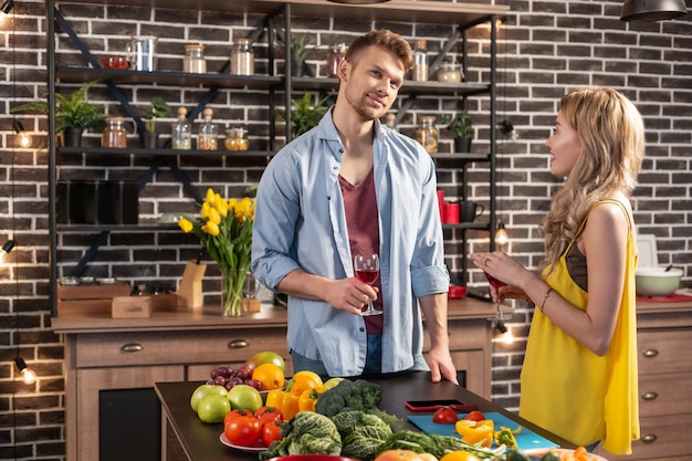 Opgewonden koppel. net getrouwd jong stel voelt zich opgewonden tijdens het samen koken en wijn drinken