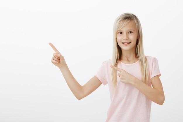Opgewonden lachend meisje vraagt om iets, wijzend in de linker bovenhoek