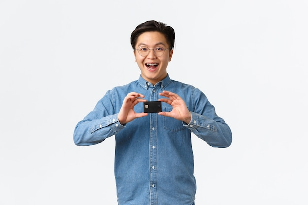 Opgewonden lachende aziatische man introduceert nieuwe bankfunctie beveel service aan die in een bril staat en br...