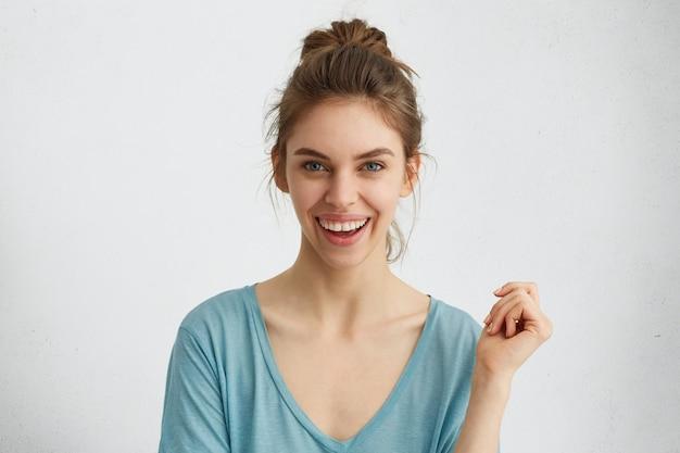Opgewonden lachende jonge vrouw met haarknoop positieve emoties uiten tijdens het poseren