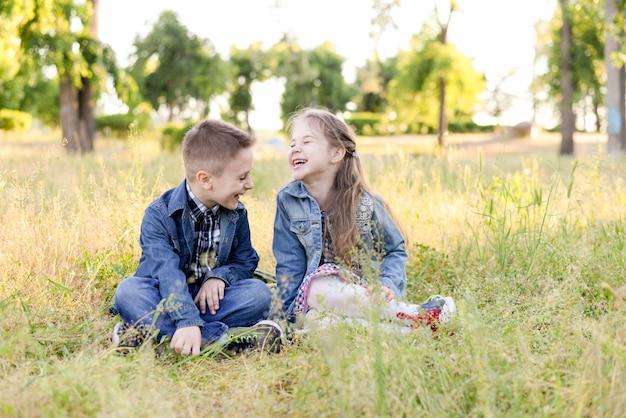 Opgewonden lachende kinderen in groen veld spelen samen