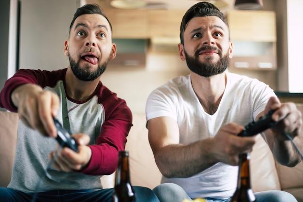 Opgewonden lachende mannen spelen in videogames op tv thuis op de bank. vrienden met joysticks spelen een spel met blije emoties op gezichten
