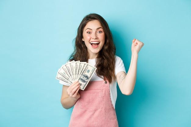 Opgewonden lachende meisjesvuistpomp en geldprijs vasthouden, geld winnen, inkomsten ontvangen van iets, blij staan tegen een blauwe achtergrond.