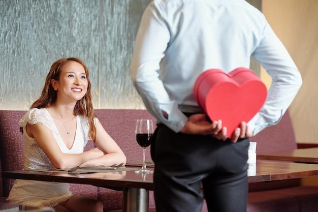 Opgewonden lachende mooie vrouw die naar vriendje kijkt die aan de tafel van het restaurant staat en het cadeau achter zijn rug verbergt