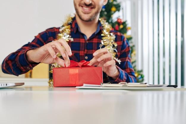 Opgewonden lachende ondernemer kerstcadeau openen bij bureau