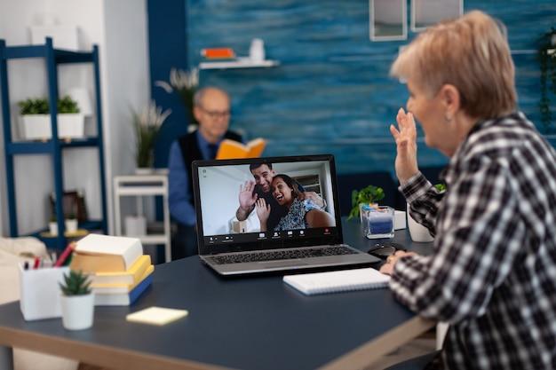 Opgewonden lachende oudere volwassen grootmoeder zwaaiend met de hand naar kinderen. gelukkige grootmoeder die hallo zegt tijdens een online videoconferentie met familie vanuit de woonkamer.