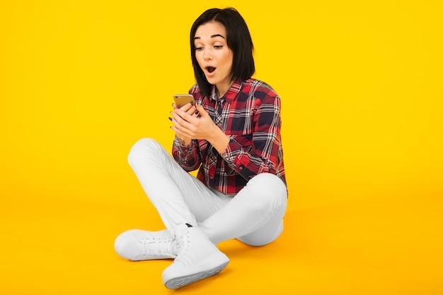 Opgewonden lachende vrouw in geruite overhemd zit en met behulp van mobiele telefoon op gele achtergrond