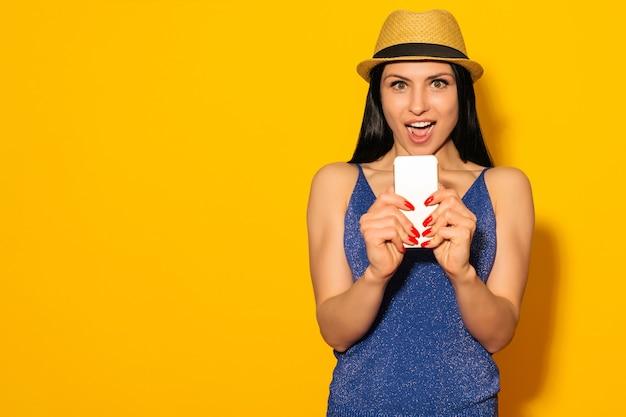 Opgewonden lachende vrouw in hoed permanent en met behulp van mobiele telefoon op gele achtergrond - afbeelding