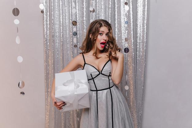 Opgewonden lieve jonge vrouw in lichte jurk verrast door haar cadeau voor nieuwjaar. foto's van europeaan in elegante kleding op een muur van glitters