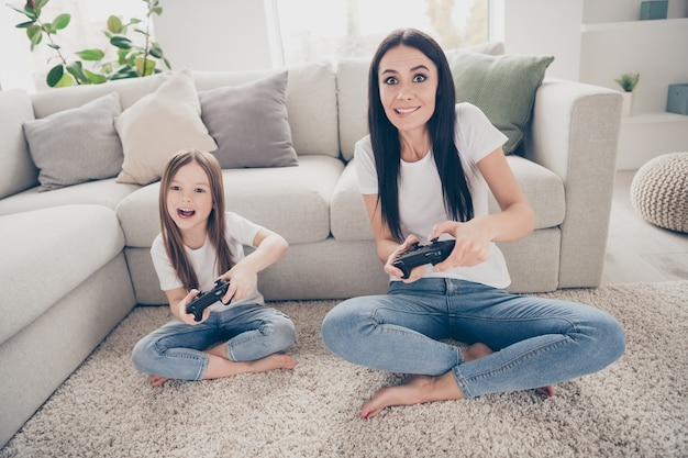 Opgewonden mama klein kind spelen videogame in kamer huis binnenshuis