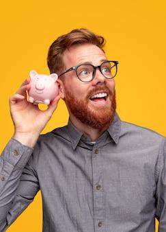 Opgewonden man die besparingen in spaarpot controleren