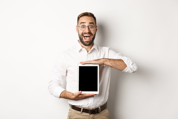Opgewonden man die het digitale tabletscherm toont, verbaasd glimlacht, staande op een witte achtergrond.