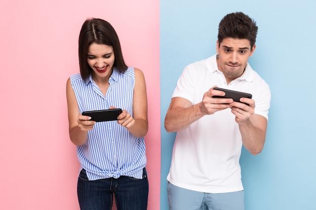 Opgewonden man en vrouw spelen samen videogames met behulp van telefoons, geïsoleerd over kleurrijke muur