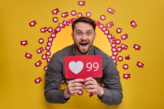 Opgewonden man houdt van knop teken in handen, liefde, bezig met actieve leiding van sociale media. gele muur