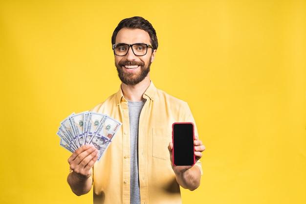 Opgewonden man in casual met veel geld in dollarvaluta's en mobiele telefoon in handen
