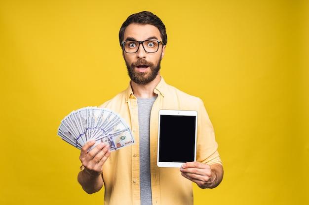 Opgewonden man in casual met veel geld in dollarvaluta's en tabletcomputer in handen geïsoleerd op gele achtergrond. tabletscherm voor tekst.