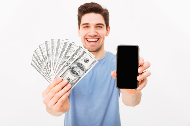 Opgewonden man in casual t-shirt toont zijn geldprijs en copyspace scherm van smartphone, geïsoleerd over witte muur