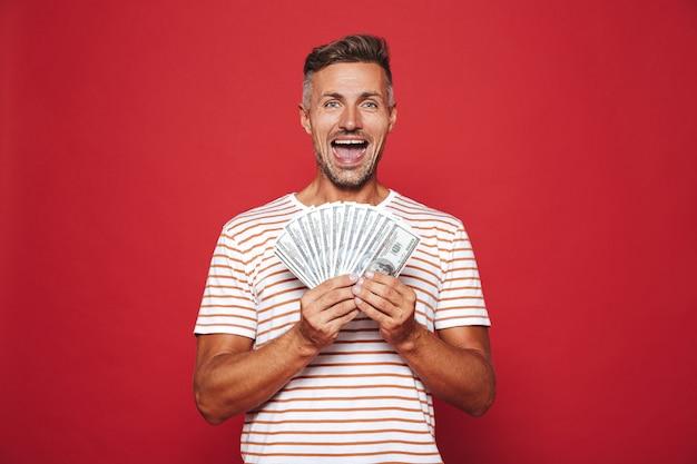 Opgewonden man in gestreept t-shirt glimlachend en met fan van geldbankbiljetten geïsoleerd op rood