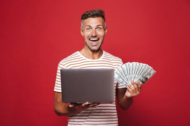 Opgewonden man in gestreept t-shirt glimlachend terwijl hij een fan van geldbankbiljetten en een laptop vasthoudt die op rood is geïsoleerd