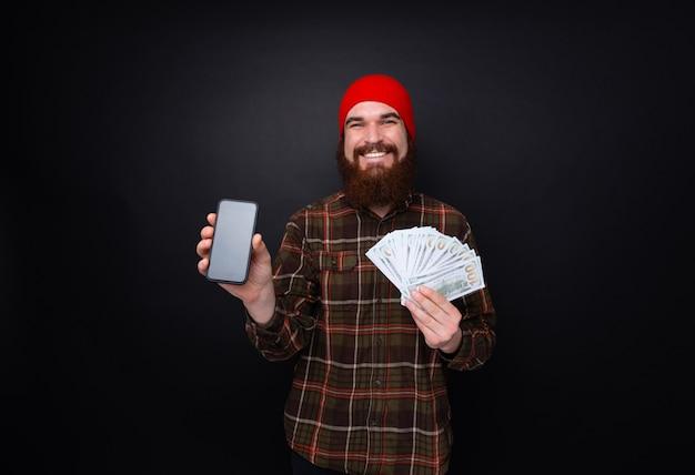 Opgewonden man in het aantonen van zijn geldprijs en copyspace scherm van smartphone geïsoleerd over donkere muur