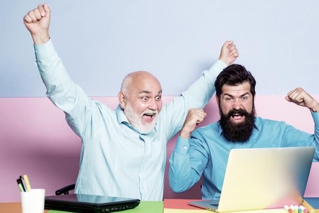 Opgewonden man kijken laptop scherm verrast door goed online nieuws.