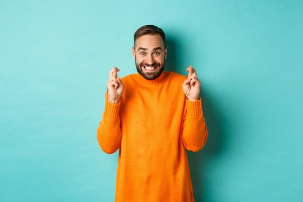 Opgewonden man met baard, die een wens doet, de vingers gekruist houdt voor geluk en glimlacht, staande over de lichtblauwe muur.