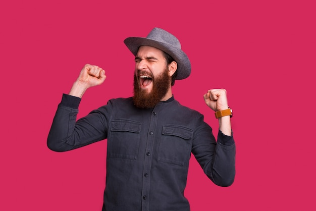 Opgewonden man met baard, een winnaar, vieren met armen omhoog en gesloten ogen