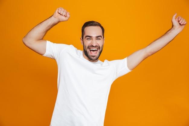 Opgewonden man met baard en snor lachend staand, geïsoleerd op geel