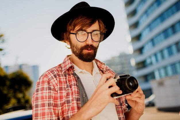Opgewonden man met baard met interessant met behulp van retro filmcamera, foto's maken