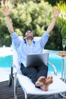 Opgewonden man met behulp van een laptop in de buurt van zwembad