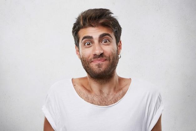 Opgewonden man met dikke donkere wenkbrauwen en baard die aangenaam verrast is en met wijd geopende ogen kijkt met een twijfelachtige blik. binnen schot van knappe kerel die uitdrukking heeft verward