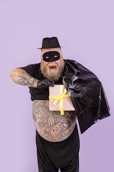 Opgewonden man met overgewicht in zorro-kostuum verbergt geschenkdoos achter cape op paarse achtergrond