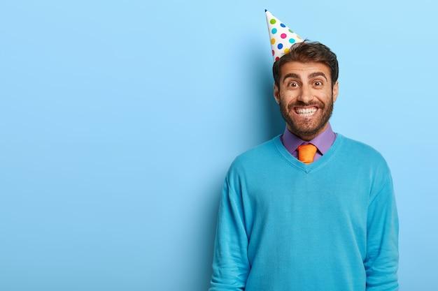 Opgewonden man met verjaardagshoed poseren in blauwe trui