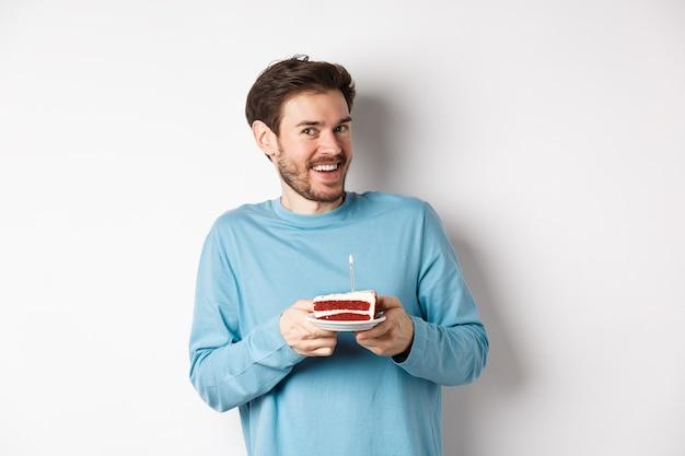 Opgewonden man ontvangt verjaardagsverrassing, houdt verjaardagstaart vast en glimlacht gelukkig, staat op een witte achtergrond en doet een wens op een verlichte kaars.