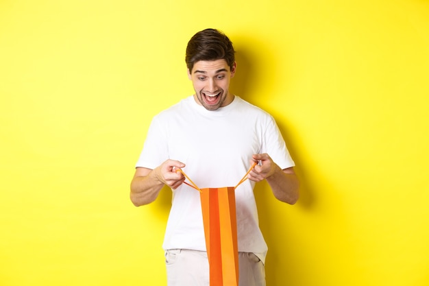 Opgewonden man open zak met cadeau naar binnen kijkend met verbazing en blij gezicht staande tegen gele ...