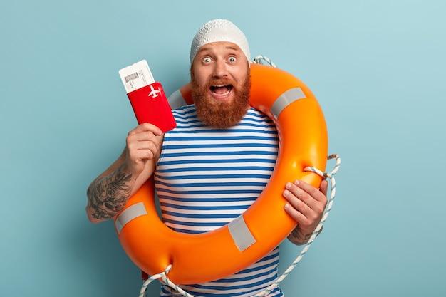 Opgewonden man toont vliegende boarding pass tickets met paspoort, draagt oranje reddingsboei, bereidt zich voor op reis naar het buitenland